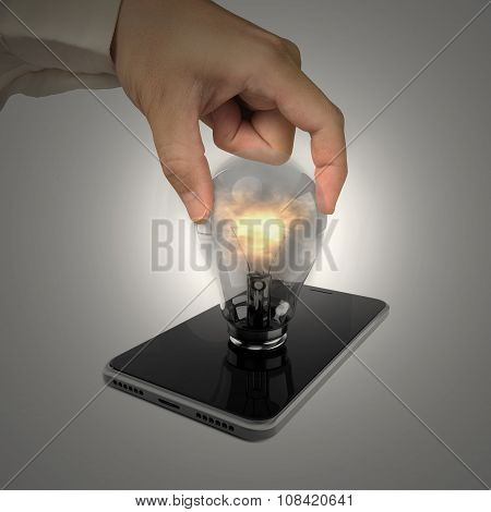 Human Hand Holding Glowing Light Bulb Inserted In Smart Phone
