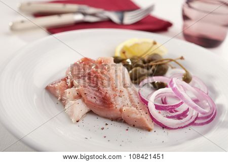 Marinated herring with red onion, capers, and lemon