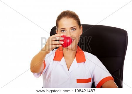 Smile female doctor or nurse sitting behind the desk and holding heart toy.