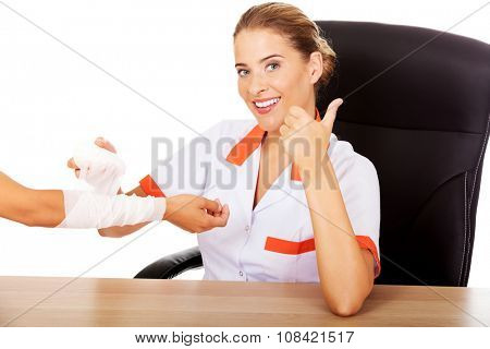 Young smile woman doctor bandaging female hand.