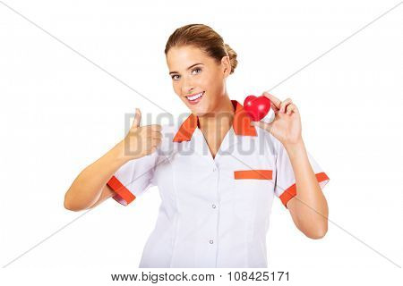 Young female doctor or nurse holding toy heart and shows thumb up.