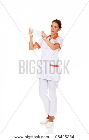 Young female nurse or doctor holding a bandage.