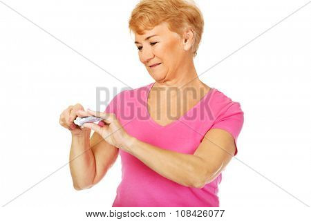 Smiling senior woman holding toothpaste and toothbrush.