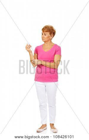 Senior woman holding medicament bottle.