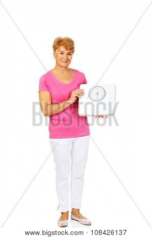 Smiling old woman holding weight scale.
