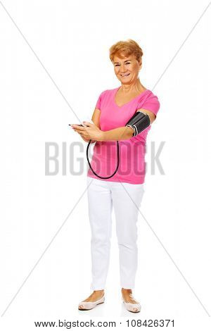 Smiling senior woman measuring blood pressure with automatic manometer.