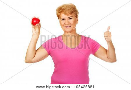 Old smiling woman holding red toy heart with thumb up.