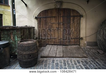 Old rusty wooden gate with barrel as a background