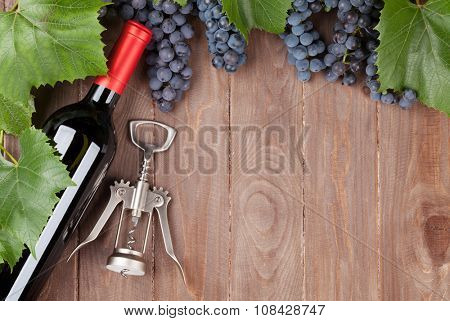 Red grape, wine bottle and corkscrew on wooden table. Top view with copy space