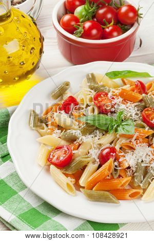 Colorful penne pasta with tomatoes and basil on wooden table