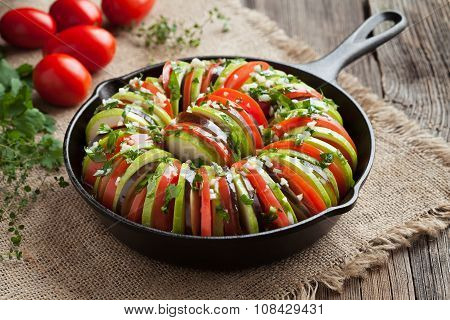Raw vegetable ratatouille in cast iron frying pan preparation recipe on vintage wooden table backgro