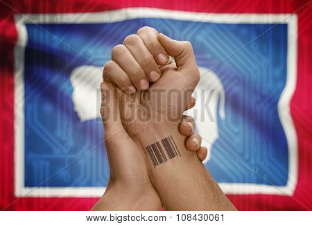 Barcode Id Number On Wrist Of Dark Skinned Person And Usa States Flags On Background - Wyoming