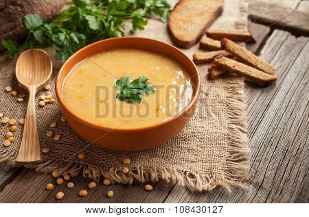Pea soup healthy vegetarian organic food recipe with croutons and greens on rustic wooden table back