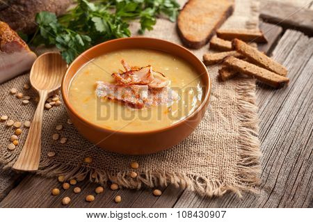 Traditional german homemade pea soup recipe with bacon and croutons in clay dish on vintage wooden t