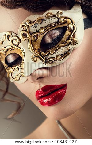Beauty model woman wearing venetian masquerade carnival mask at party over holiday dark background. Christmas and New Year celebration. Glamour lady with perfect make up and hairstyle