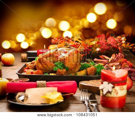 Christmas Dinner. Roasted Turkey on holiday served table. Thanksgiving table served with turkey, decorated with bright autumn leaves and candles. Roasted chicken, table setting.