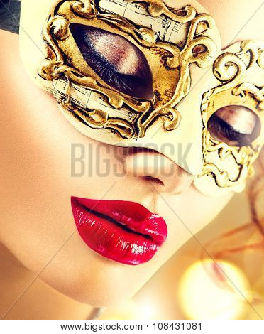 Beauty model woman wearing venetian masquerade carnival mask at party over holiday glowing gold background. Christmas and New Year celebration. Glamour lady with perfect make up