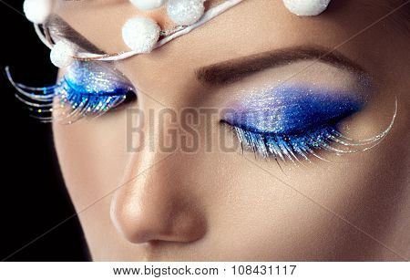 Winter Christmas eyes make up with glitter blue eyeshadows and false eyelashes. Party art model Woman makeup. Creative Girl Holiday Make-up. Snow Queen High Fashion Portrait over Black Background
