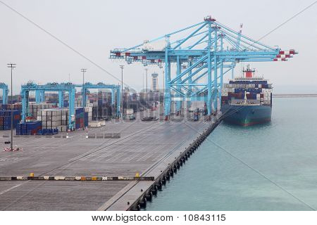 Men Load Big Cargo Boat Docked To Industrial Port With Blue Cranes