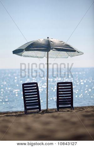 Near  Sea Ashore Two Dark Blue Plastic Chairs Stay Under  Large Umbrella