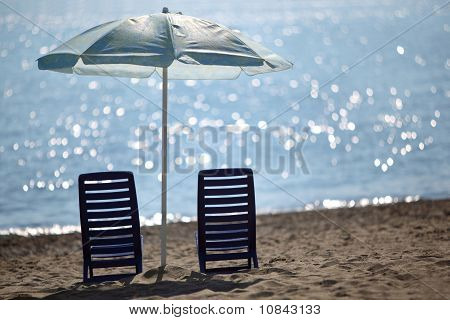 Two Dark Blue Empty Chairs  Stand On  Beach Near  Sea Under Shade Of Large Umbrella