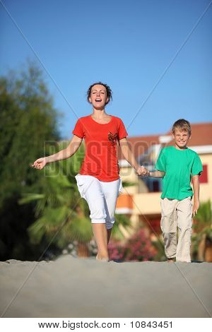 Woman With  Son Holding On To Hands Hurry On  Beach By  Bright Sun Day