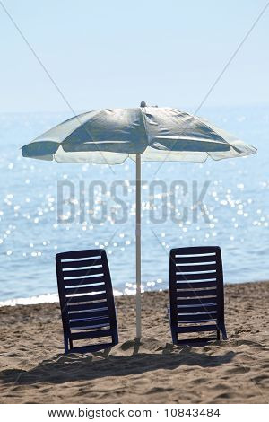 Two Dark Blue Plastic Chairs Stand In Kontrazhure On  Beach, Near Water Under  Large Blue Umbrella