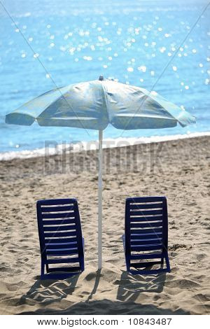Ashore  In  Day-time On Sand Two Empty Plastic Chairs Cost Under  Beach Umbrella