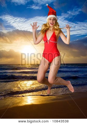 The girl in a suit of Santa Claus jumps on an ocean coast during a sunset
