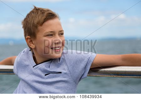 Smiling boy on the promenade by the sea