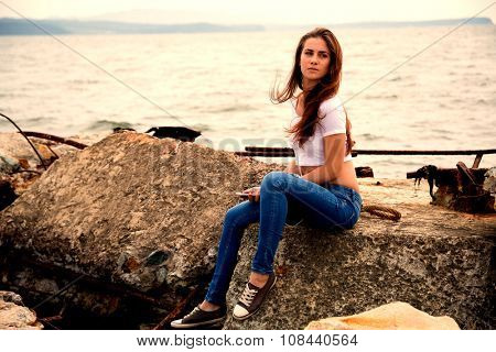 Beautiful girl using smartphone sitting on an old concrete pier. Image retro vintage filter effect.
