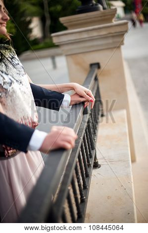 A loving couple standing arm in arm leaning on the railing arms