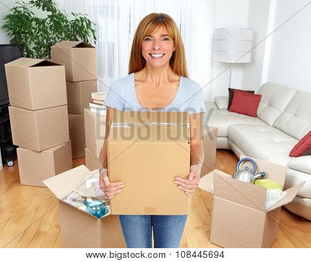Beautiful smiling  lady with moving box in a new apartment.