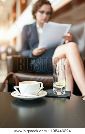 Coffee Cup And Glass Of Water At Cafe With Businesswoman