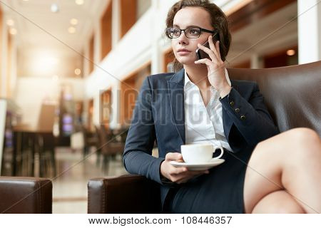 Businesswoman Sitting At Coffee Shop Using Mobile Phone