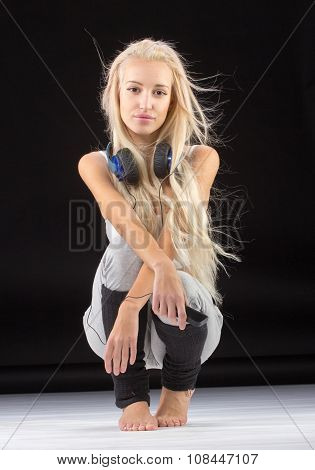 Young slim fitness woman sitting on knees in studio with earphones