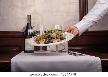 A waiter delivers a salad with meat and lettuce on a plate in rekstorane, glass of white wine
