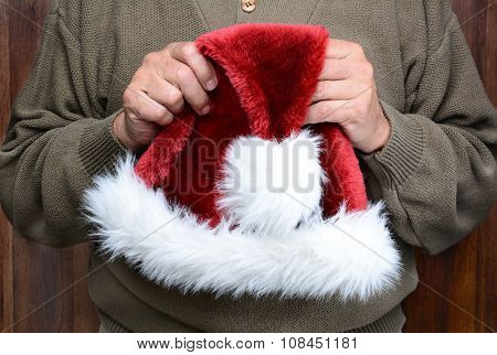 A man wearing a green sweater holding a Santa Claus hat in front of his torso. Man is unrecognizable. Horizontal format.