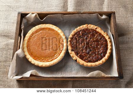 High angle view of a fresh baked pumpkin pie and a pecan pie in a wood box on burlap covered table, for Thanksgiving feast.