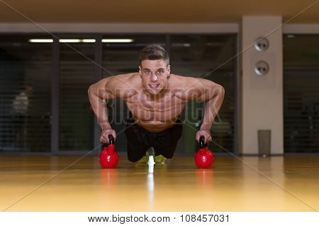 Young Man Exercising Push Ups On Kettle Bell