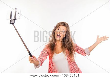 Happy Nice-looking Young Woman  With Hat Making Selfie Photo With Stick