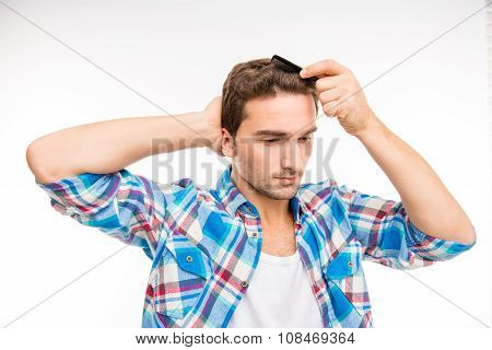 Calm Young Man Combing His Hair