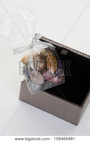 Small Colorful Chocolate Stones On Grey Box