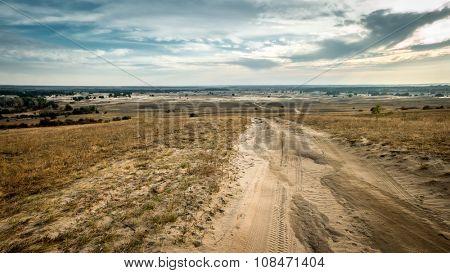 landscape of rolled road in a sandy field