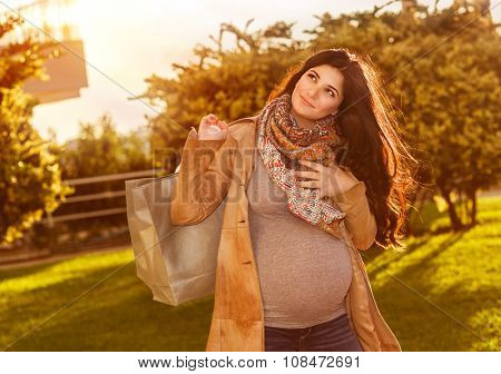 Happy pregnant woman with shopping bag in sunny autumn day on the backyard, preparing to baby birth, enjoying last days of pregnancy