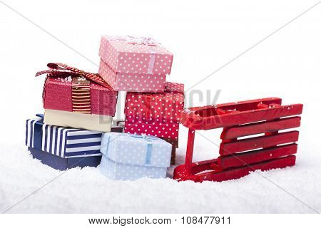 Red sled and gift boxes on white background