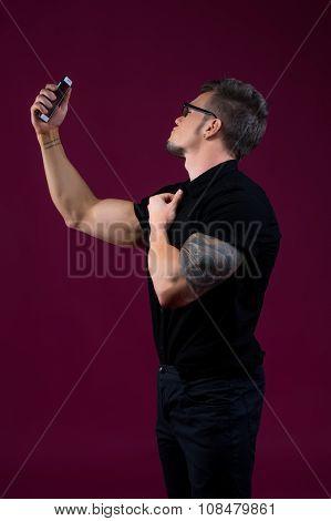 Stylish bodybuilder doing selfie with smartphone