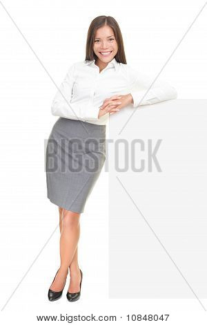 Young Businesswoman Leaning On Sign
