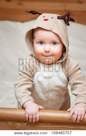 Cute little baby girl wearing christmas deer costume looking at camera