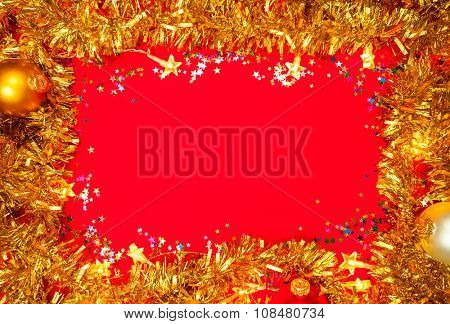Christmas baubles with star-shaped lights and tinsel frame on red background